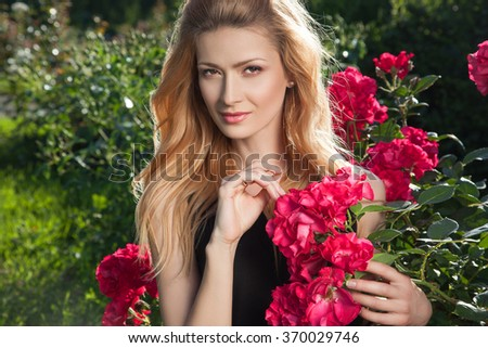 Beautiful young woman on a walk, the girl in flowers. Stylish fashionable woman in the highlights.Beautiful young woman and flowers.