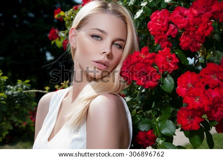 Beautiful young woman on a walk, the girl in flowers. Young blonde with nice make-up on her face in the background with red roses. Portrait of girl in roses. Woman and flowers - stock photo