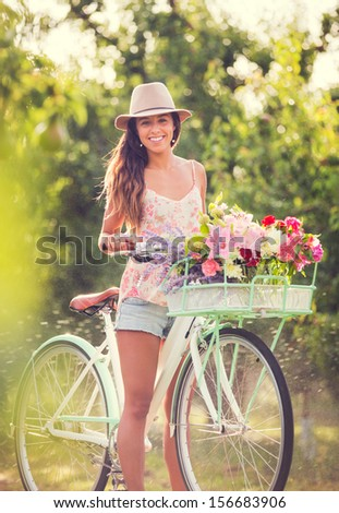 Beautiful young woman on bike in park - stock photo