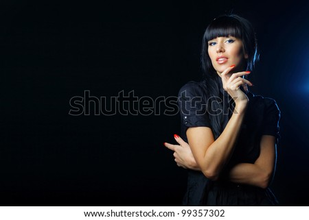 Beautiful young woman on black background pointing at copyspace - stock photo