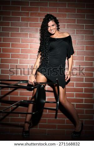 beautiful young woman on brick wall. beautiful figure, long hair, bright emotions - stock photo
