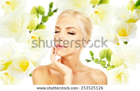 Beautiful young woman on freesia flower background - stock photo