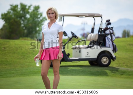 Beautiful young woman on golf course with drink