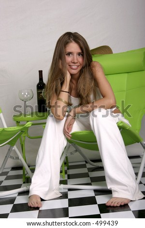 Beautiful young woman on green chair - stock photo