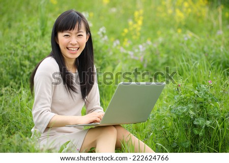 Beautiful young woman on green field. Portrait of asian.