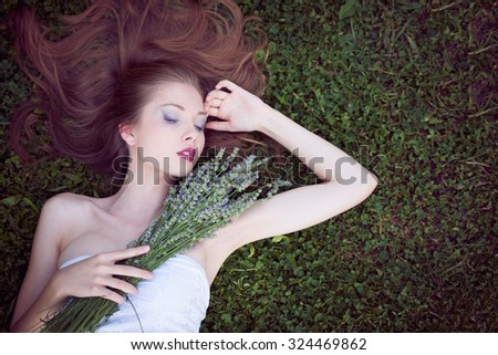 Beautiful young woman on lavender field - stock photo