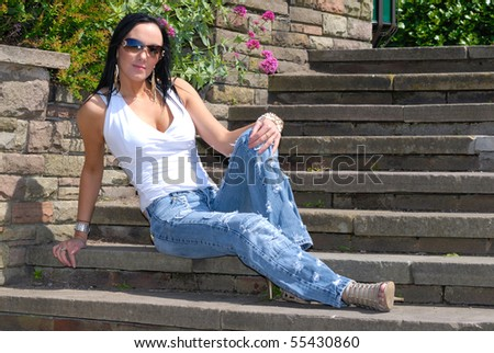 Beautiful young woman on park steps