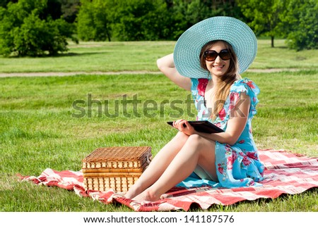 Beautiful young woman on picnic working on tablet - stock photo