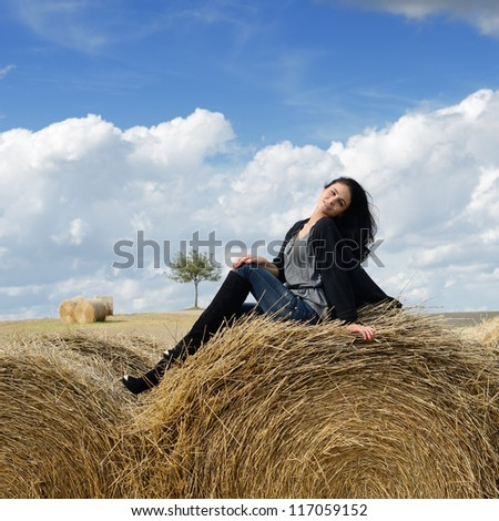 Beautiful young woman on stack of hay on autumn day in the country, Tuscan, Italy - stock photo