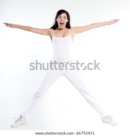 beautiful young woman on studio isolated white background doing her workout stretch jump happy - stock photo