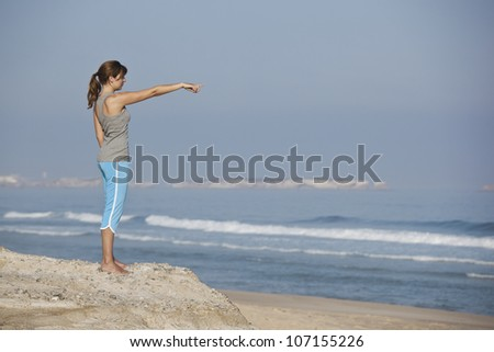 Beautiful young woman on the beach looking to the ocean