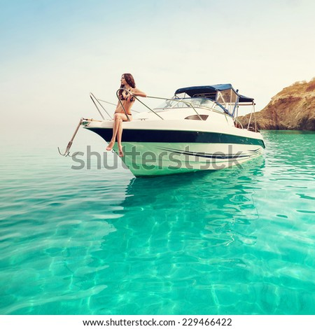 Beautiful young woman on the boat a sunny summer day. Luxury vacation at sea on the yacht. - stock photo