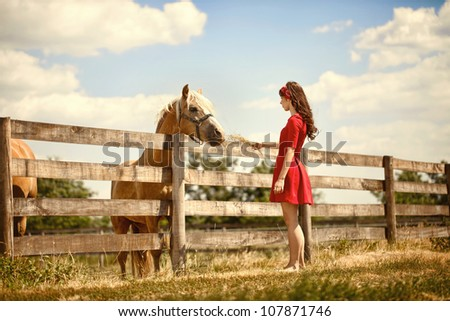 Beautiful young woman on the farm with her horse.