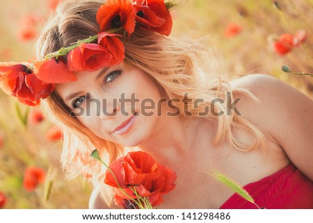 Beautiful young woman on the poppy field