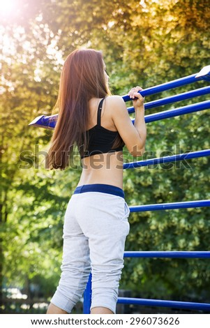 Beautiful young woman on the sports ground. Exercise outdoors