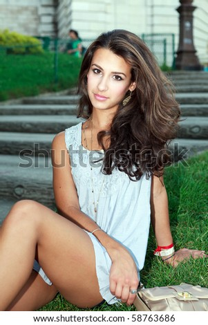 Beautiful young woman on the steps of the Sacre-Coeur Basilica in the Montmartre area in Paris, France. - stock photo