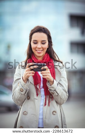 Beautiful young woman on the street text messaging.  - stock photo