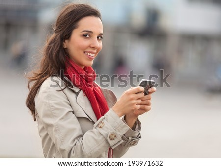 Beautiful young woman on the street with smart phone. - stock photo