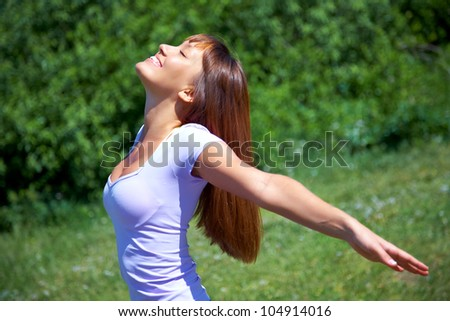 beautiful young woman opened her hands against at green park - stock photo