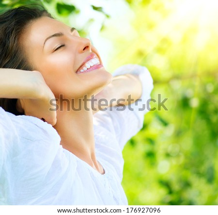 Beautiful Young Woman Outdoor. Enjoy Nature. Healthy Smiling Girl in the Spring Park. Sunny day
