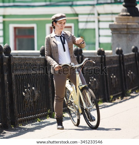 """Beautiful young woman outdoors riding vintage bicycle, looking at wrist watch. Girl wears british style """"tweed ride"""", brown plaid jacket and flat cap - stock photo"""