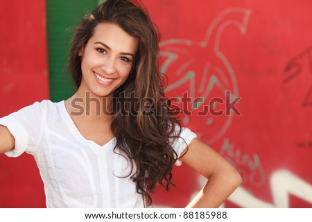 Beautiful young woman outdoors with a red graffiti background. - stock photo