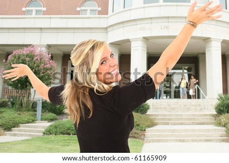 Beautiful young woman outside happy to be at collage. - stock photo