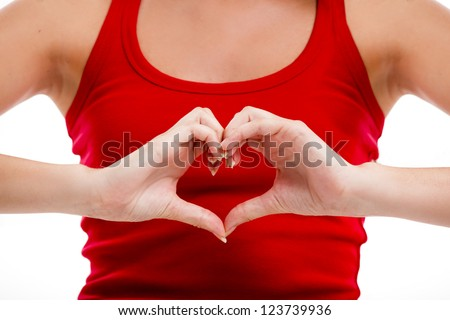 Beautiful young woman over a white background doing a heart shape with her hands - stock photo