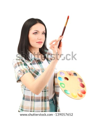 Beautiful young woman painter with brushes and palette at work, isolated on white