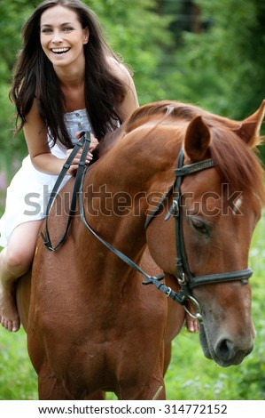 beautiful young woman park riding horse - stock photo