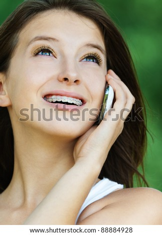 beautiful young woman park talking phone looking up - stock photo