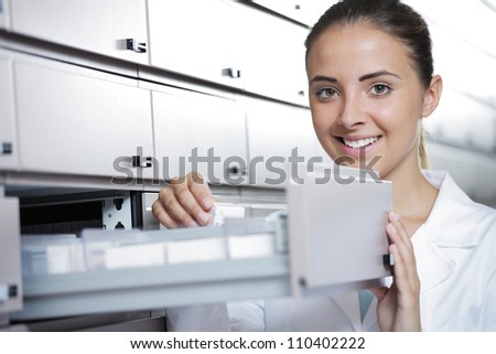 Beautiful young woman pharmacist reaching for medicine - stock photo