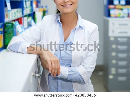 Beautiful young woman pharmacist standing at her workplace in pharmacy. - stock photo