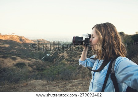 Beautiful young woman photographer hiker taking selfie on the top of a mountain peak at Hollywood hills when hiking and shooting - stock photo