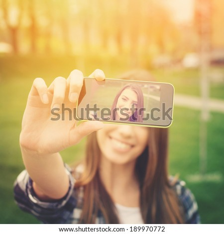 Beautiful young woman photographing herself with phone. Cute smiling young Caucasian teenage girl taking a selfie outdoors on sunny summer day. - stock photo