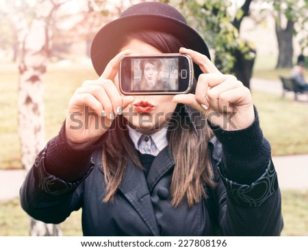 Beautiful young woman photographing herself with phone,selective focus - stock photo