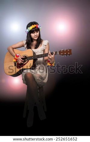 Beautiful young woman playing an acoustic guitar - stock photo