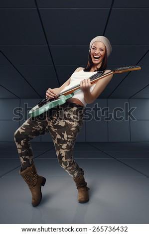 Beautiful young woman playing rock guitar and singing - stock photo