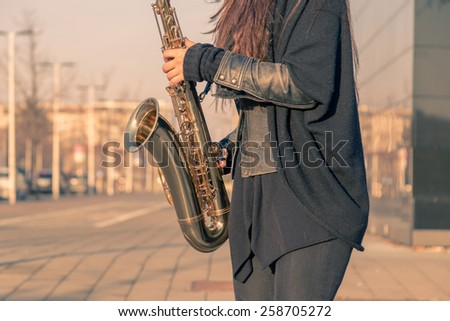 Beautiful young woman playing tenor saxophone in the city streets