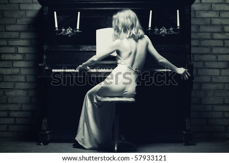 beautiful young woman playing the piano (black and white photo) - stock photo