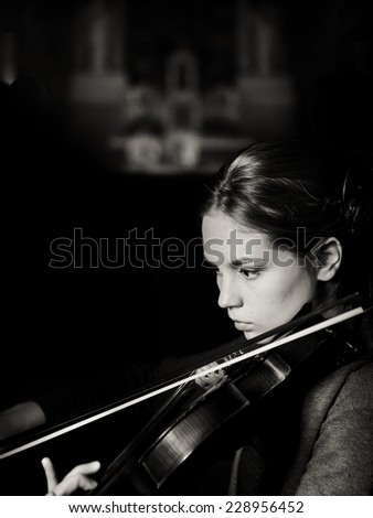 Beautiful young woman playing violin. Violinist woman playing violin live. Musician performer playing violin. Romantic surprise for your loved one. Violinist playing in church orchestra - stock photo