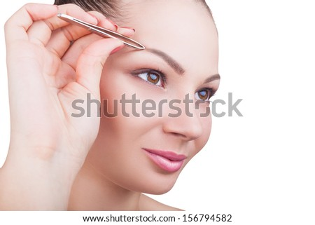 Beautiful young woman plucks eyebrows isolated on white background - stock photo