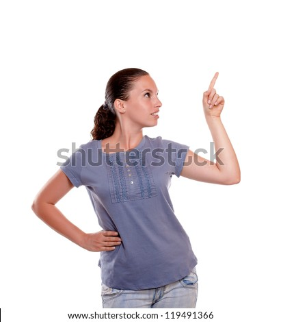 Beautiful young woman pointing and looking to her left on blue shirt at isolated background - copyspace - stock photo