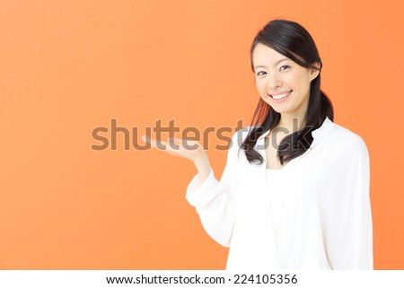 beautiful young woman pointing copy space against orange background - stock photo