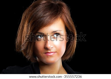Beautiful young woman portrait on dark background - stock photo