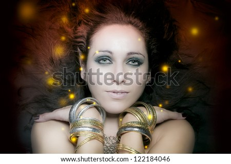 beautiful young woman portrait with long, mysterious lights floating around her - stock photo