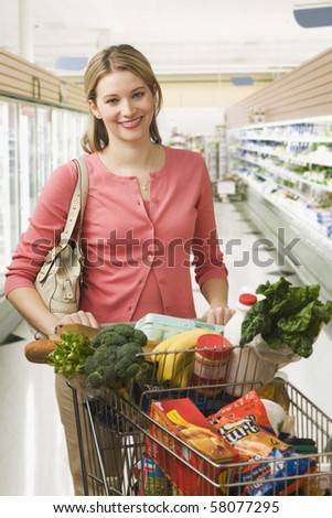 Beautiful young woman poses in a grocery store with a shopping cart full of food.  Vertical shot. - stock photo
