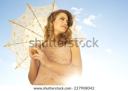 beautiful young woman poses with umbrella with a sunshine sky in the background. useful for health and beauty, lifestyle and fashion  - stock photo