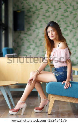 Beautiful young woman posing alone in the cafe, Model is Thai Ethnicity. - stock photo