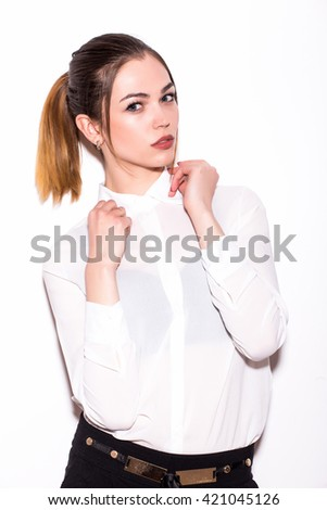 Beautiful young woman posing and looking at camera while standing against white background